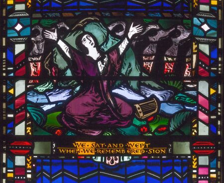 LONDON, GREAT BRITAIN - SEPTEMBER 16, 2017: The scene of The sorrow in the captivity of the Jews in Babylon on the stained glass in church St Etheldreda by Charles Blakeman (1953 - 1953). Editorial