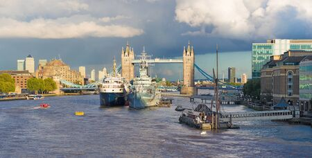 London - The panorama of the Tower bridge, riverside in evening light with the dramatic clouds.