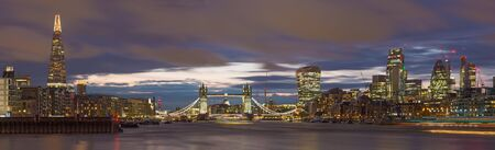 London - The panorama of the Tower bridge, riverside and skyscrapers at dusk with the dramatic clouds. Stock Photo