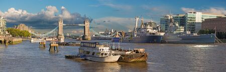 London - The panorama of the Tower bridge, riverside and cruiser Belfast in evening light with the dramatic clouds.