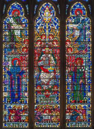 LONDON, GREAT BRITAIN - SEPTEMBER 16, 2017: The stained glass of Jesus Christ the Pantokrator, Virgin Mary, St. Joseph and the Evangelists in church St Etheldreda by Joseph Edward Nuttgens (1952).