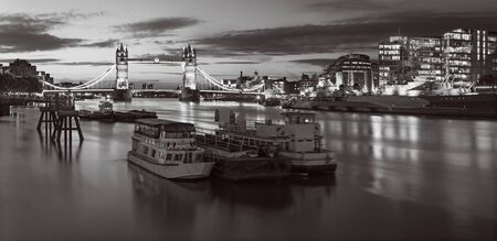 London - The panorama with the Tower bridge, riverside in morning dusk with the dramatic clouds. Stock Photo