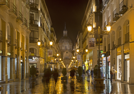 ZARAGOZA, SPAIN - MARCH 1, 2018: The cathedral  Basilica del Pilar and Calle de Alfonso I at rainly night.