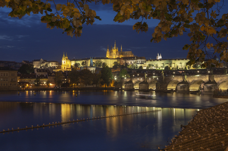 Prague - The Charles Bridge, Castle and Cathedral from promenade over the  Vltava river at dusk.