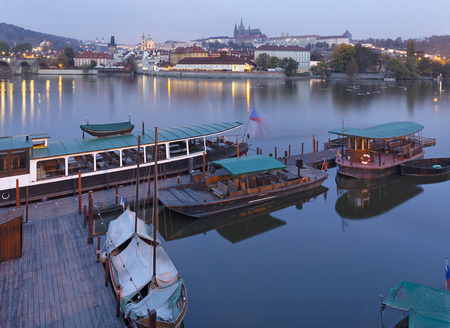 Prague - Charles bridge, castle and cathedral with the little harbor at dusk. Editorial