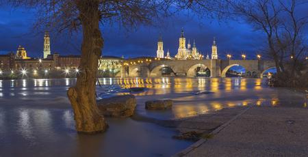 Zaragoza - The bridge Puente de Piedra and Basilica del Pilar with the riverside of Ebro river at dusk.