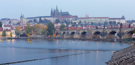 Prague - The Charles Bridge, Castle and Cathedral from promenade over the  Vltava river at the morning dusk.