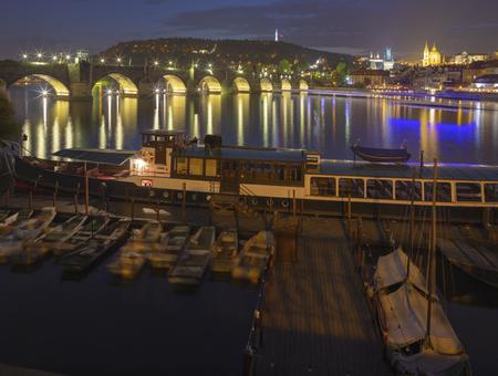 Prague - Charles bridge and St. Nicholas church with the little harbor at dusk.