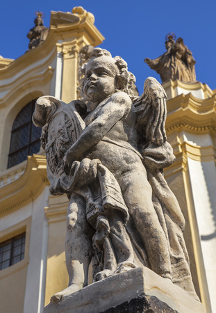 Prague - The baroque angel and  facade of  Loreto church  - designed by Kilian Ignac (1772).