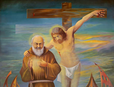 REGGIO EMILIA, ITALY - APRIL 12, 2018: The detail of modern painting of Pater Pio with the Jesus on the corss in church Chiesa dei Cappuchini by Erico Verona 2001.