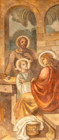 BARCELONA, SPAIN - MARCH 3, 2020: The fresco of Holy family in Nazareth in the church Parroquia Santa Teresa de l'Infant Jesus by Francisco Labarta (20. cent.).