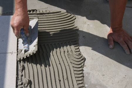 grout: On this picture is hands, that work with grout.