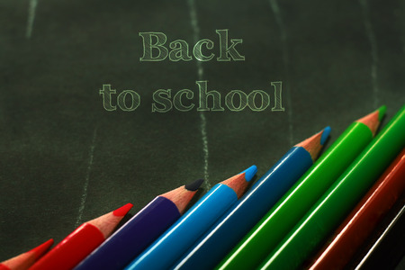 Photo of crayons on black backdrop with inscription Back to school