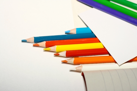 Photo of crayons on exercise book and a paper