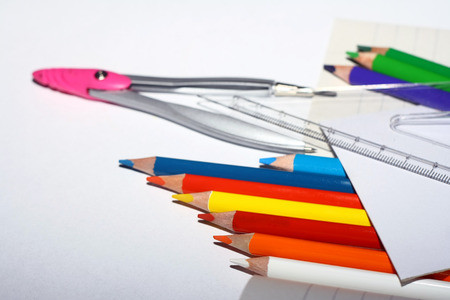 Photo of crayons with ruler and compass on exercise book and a paper