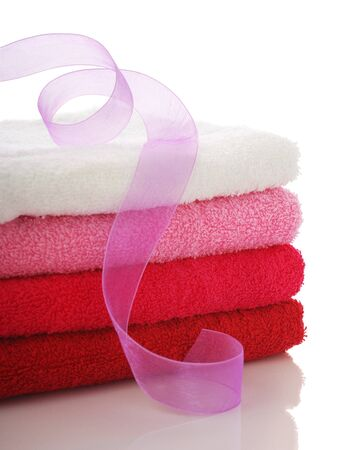 Stack of clean towels and pink ribbon. Isolated on white Фото со стока