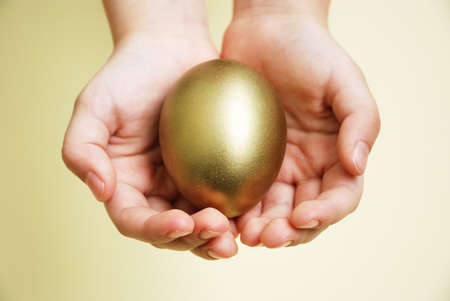 Hands of a child holding golden egg. Selective focus. photo