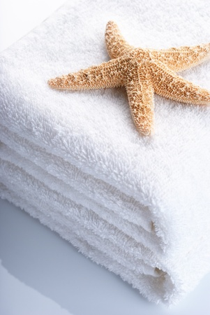 Starfish on stack of white towels with reflection.  Stock Photo