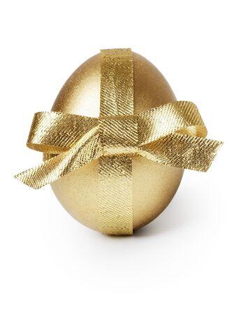 Golden egg and ribbon isolated over white Фото со стока