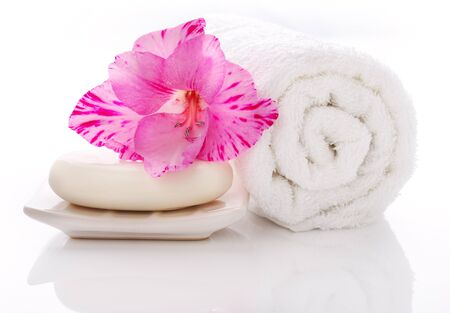 Rolled white towel, soap bar and purple gladiolus flower.