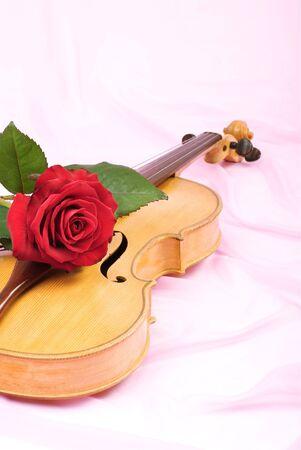 Old viola, red rose, and vintage music sheet