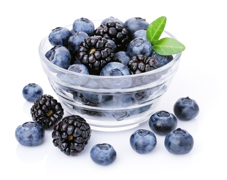 Glass of delicious blueberries and blackberries. Isolated on white