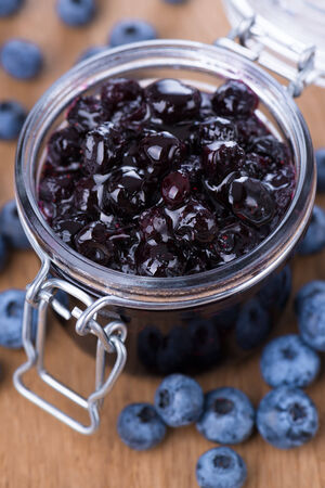 Jar of blueberry jam and some fresh berries on wooden background