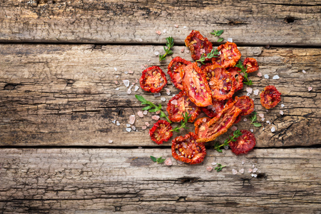 dried herbs: Heap of freshly dried tomatoes on wooden background