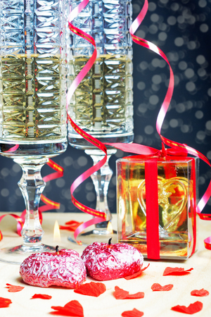 newyear night: Flutes of champagne in holiday setting. Romantic evening , candles and gift. With boke in the background