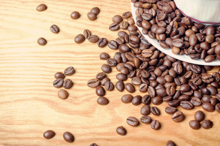 coffeetree: Fresh coffee beans on a wooden background for the preparation of delicious coffee, with a mug and saucer. Chocolate toning