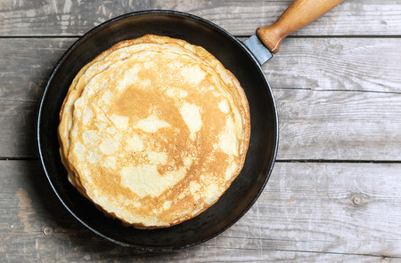 in top: Stack of pancakes on a cast-iron frying pan. Top view