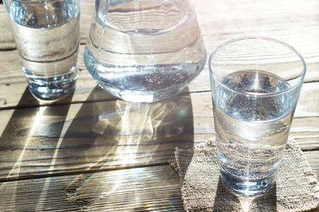purified: Glasses of water on a wooden table. Selective focus. Shallow DOF. With light effects.