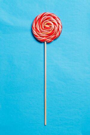 lolli: Lollipop on a stick on a blue background. Flat lay. Shallow DOF