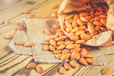 Almonds, poured out of a paper bag. Stock Photo