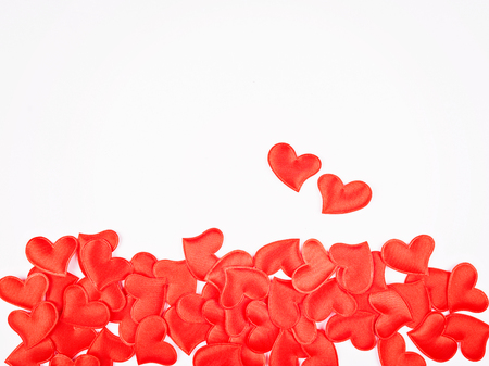 Red fabric volumetric hearts poured on a white background. Borde