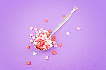 Vintage spoon with small pink, white, red sweet hearts on pastel
