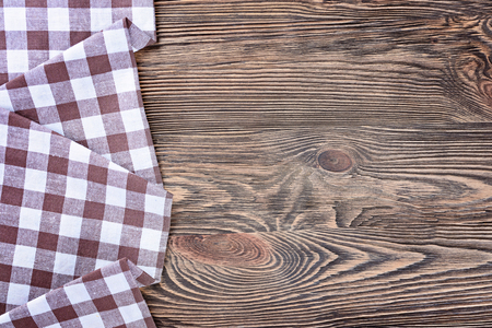 Tovagliolo di lino a scacchi su un tavolo di legno. Visualizza in alto.