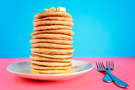 stack of pancakes on pink and blue background