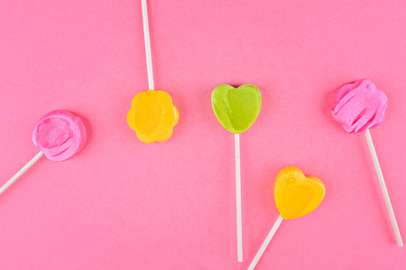 Lollipops of yellow, pink, green colors on wooden stick in the shape of circle, heart, flower.