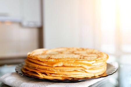 Stapel frische Pfannkuchen auf dem Küchentisch. Vor dem Hintergrund des Fensters mit Sonnenlicht. Standard-Bild