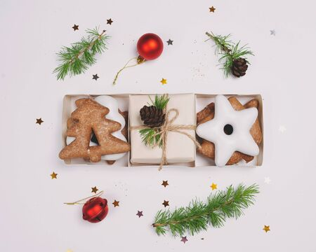 Gingerbreads in the shape of Christmas symbols, with confetti-stars, with cones and fir branches.