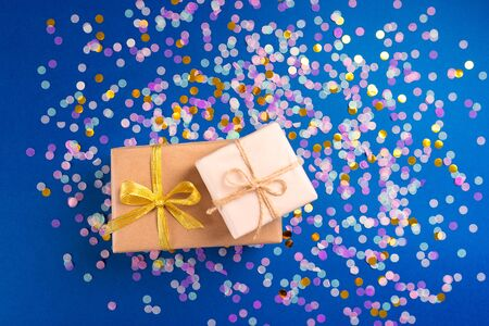 Two boxes with gift on festive paper blue background with confetti. Flat lay