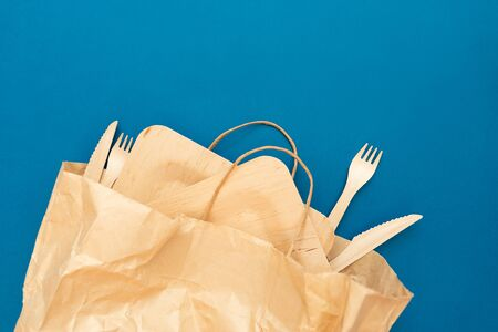 Wooden plates, forks, knives in a paper bag for food. Zero waste. Flat lay