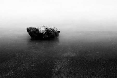 stone on the beach , black and white
