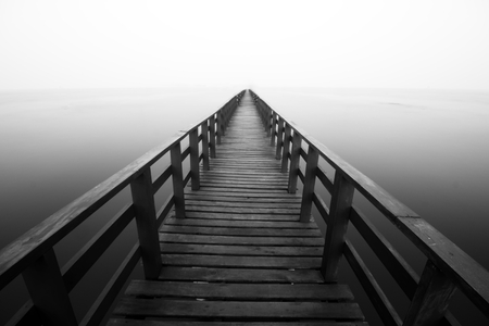 black and white Long wooden jetty disappearing into the sea photo