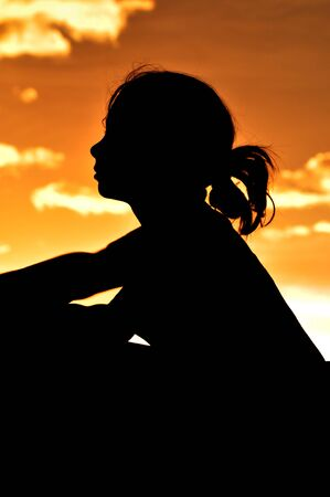 A young girl looking out over sunrise silhouette