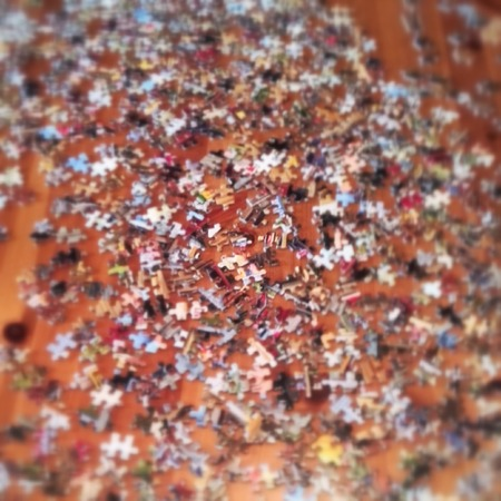 jig: Confusion concept. Blurred jig- saw puzzle pieces spread out. Stock Photo