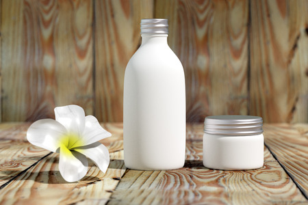Cosmetic  packaging template white  silver screw cap set with white flower on wood table organic feeling 3d rendered 版權商用圖片