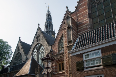 the old church: Amsterdam, view along the Oudekerksplein on the oldest preserved building in Amsterdam, Oude Kerk (Old Church), with the baroque spire in the background Stock Photo