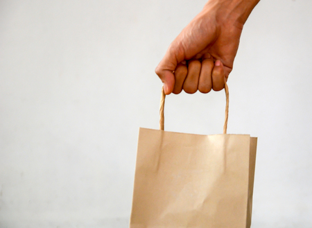 Brown Bag,Hand holding a paper bag isolated on white background. Delivery concept